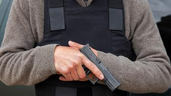 Holding pistol while wearing body armor.