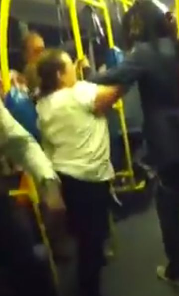 The pair exchange blows before the man shoves the woman out of the bus