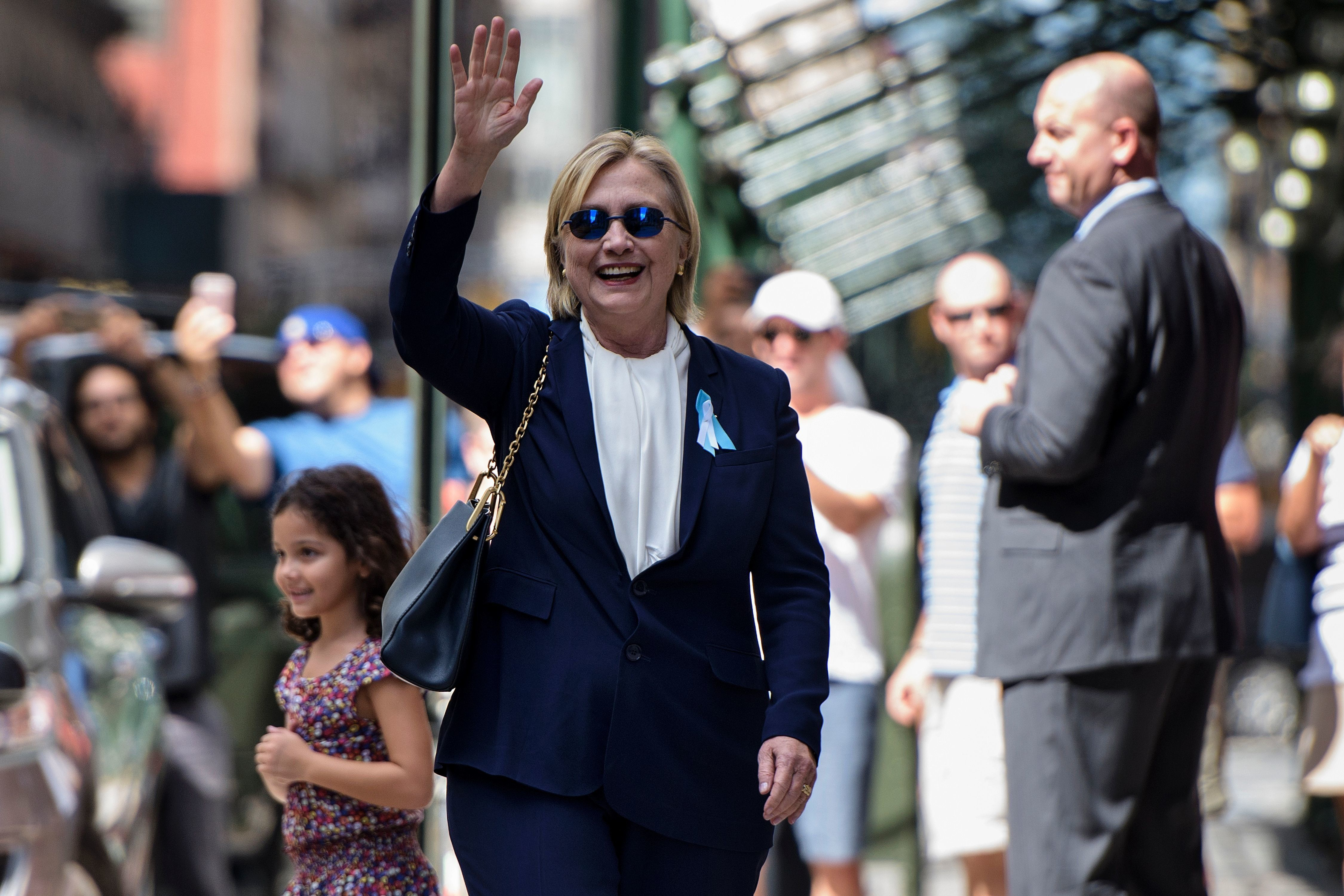 TOPSHOT - US Democratic presidential nominee Hillary Clinton waves to the press as she leaves her daughter's apartment building after resting on September 11, 2016, in New York. Clinton departed from a remembrance ceremony on the 15th anniversary of the 9/11 attacks after feeling 'overheated,' but was later doing 'much better,' her campaign said. / AFP / Brendan Smialowski        (Photo credit should read BRENDAN SMIALOWSKI/AFP/Getty Images)