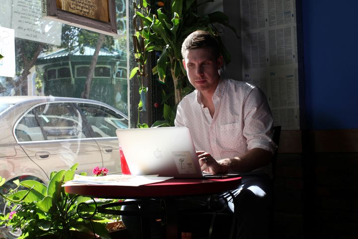 Reuters journalist Nick Brown works at his laptop at a cafe in San Juan, Puerto Rico, August 8, 2016. Picture taken August 8, 2016. (REUTERS/Alvin Baez)