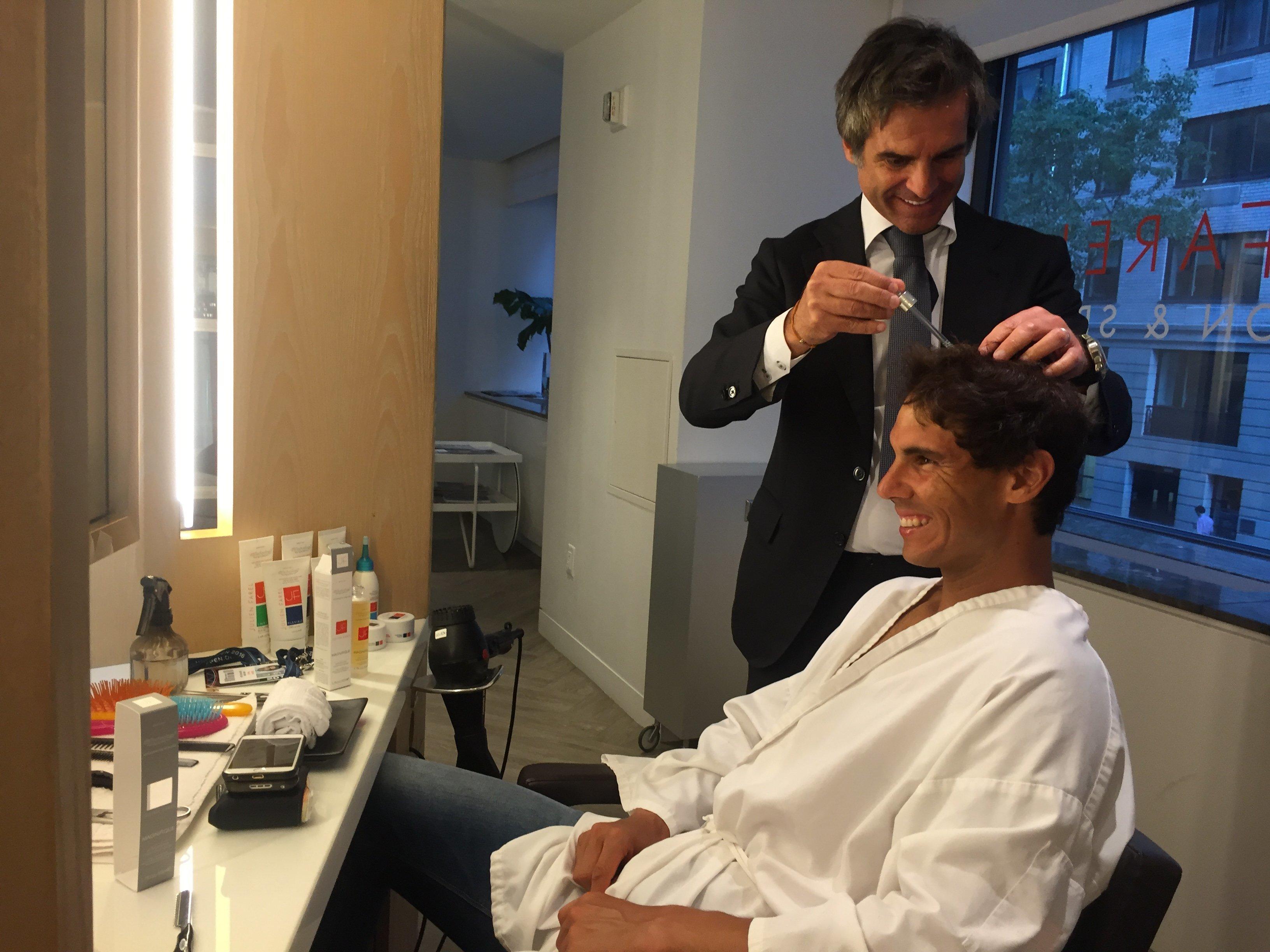 Julien Farel trimming Rafael Nadal's hair.