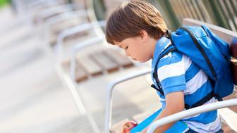 sad schoolboy waiting in the schoolyard,selective focus