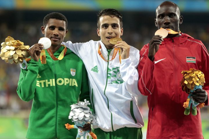 Silver medalist Tamiru Demisse, gold medalist Abdellatif Baka and bronze medalist Henry Kirwa celebrate on the podium at the