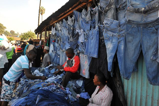 A man samples secondhand clothes (locally known as mitumba) at the Gikomba open-air market on June 25,...