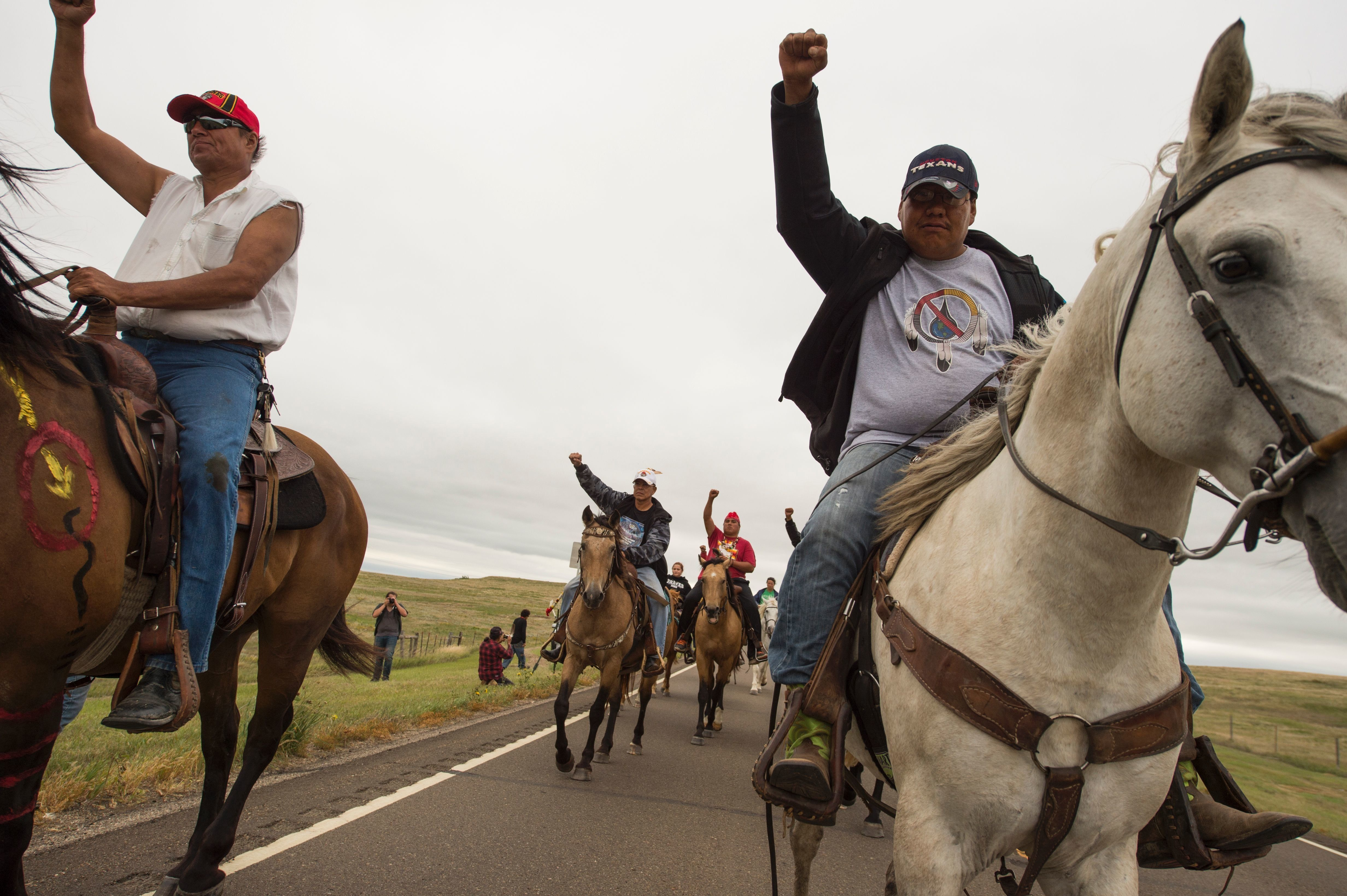 Native Americans ride with raised fists to a sacred burial ground that was disturbed by bulldozers building the Dakota Access