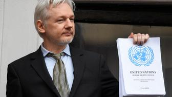 WikiLeaks founder Julian Assange holds a copy of a U.N. ruling as he makes a speech from the balcony of the Ecuadorian Embassy, in central London, Britain February 5, 2016. Assange should be allowed to go free from the Ecuadorian embassy in London and be awarded compensation for what amounts to a three-and-a-half-year arbitrary detention, a U.N. panel ruled on Friday.      REUTERS/Toby Melville  TPX IMAGES OF THE DAY