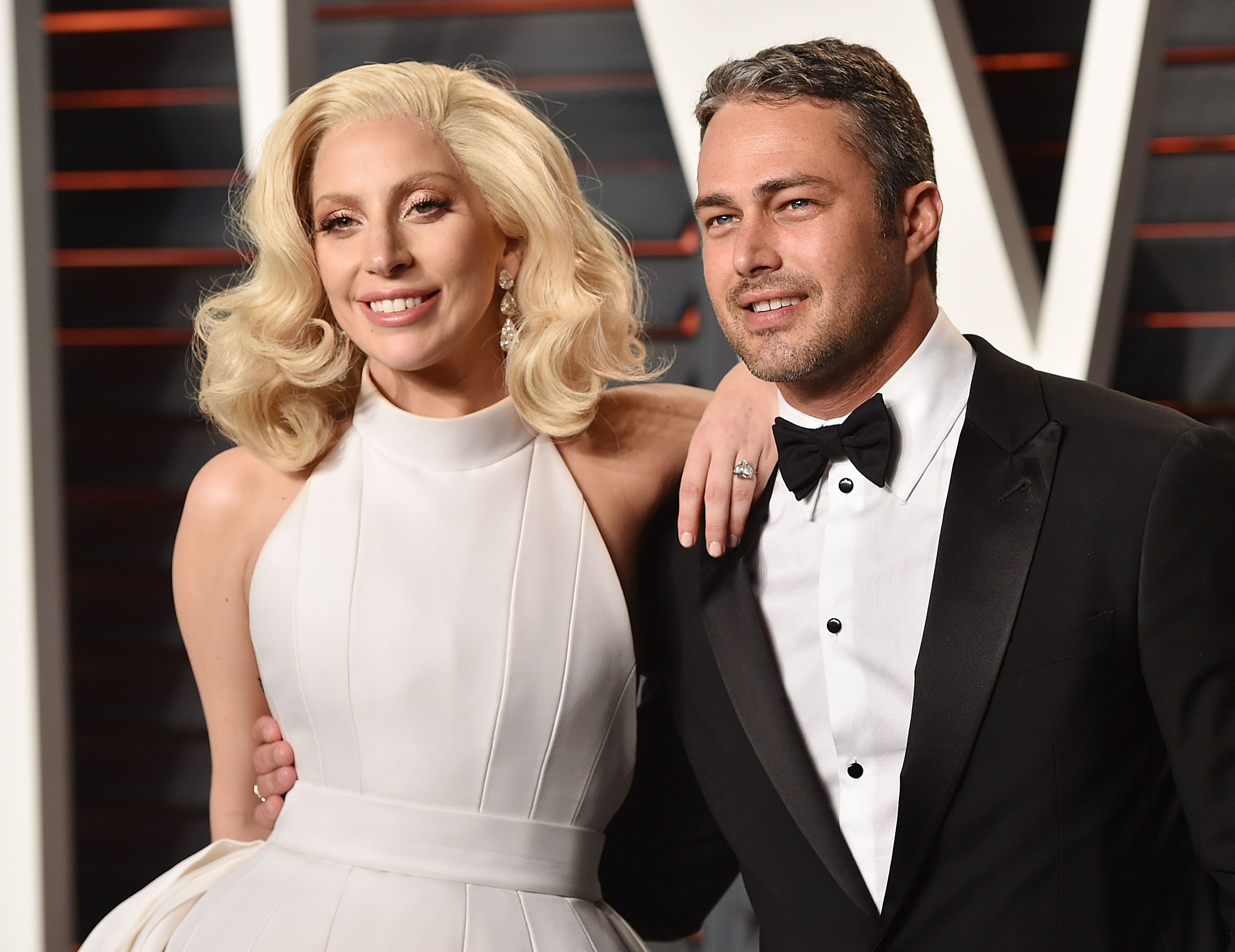 BEVERLY HILLS, CA - FEBRUARY 28:  Recording artist Lady Gaga, left, and Taylor Kinney arrive at the 2016 Vanity Fair Oscar Party Hosted By Graydon Carter at Wallis Annenberg Center for the Performing Arts on February 28, 2016 in Beverly Hills, California.  (Photo by John Shearer/Getty Images)