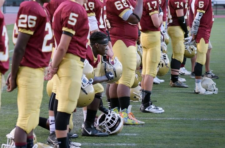 Doherty High School football player Michael Oppong on one knee during playing of the national anthem before the teams game ag