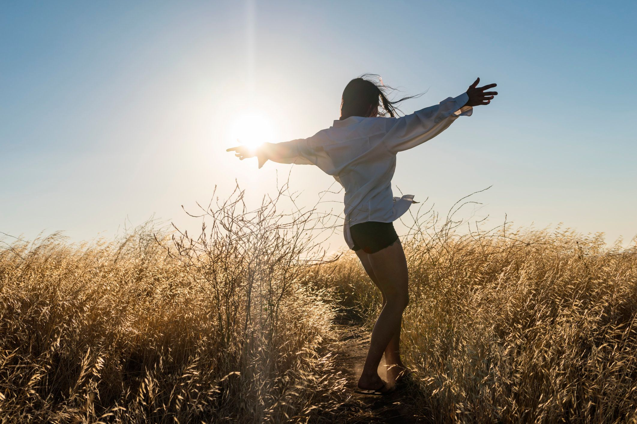 Woman dancing in a field of golden grass in sun drenched hills of California.