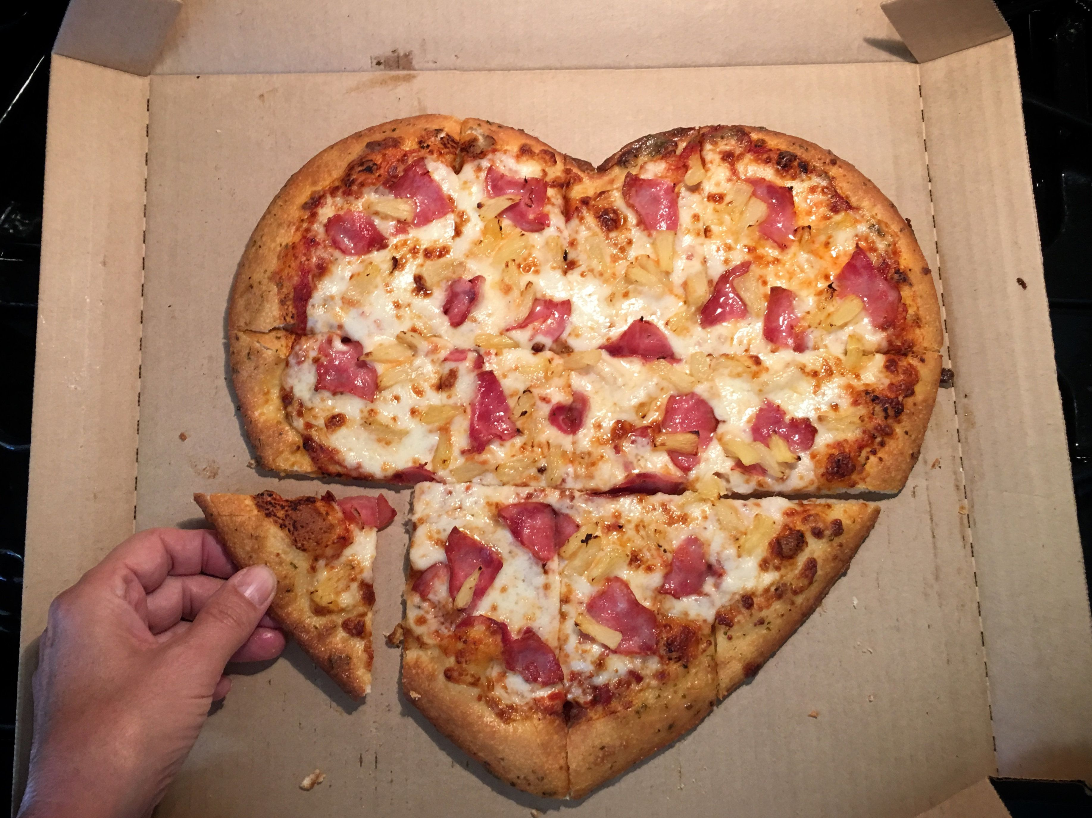 Eating a Hawaiian heart-shaped pizza with Canadian bacon and pineapple.