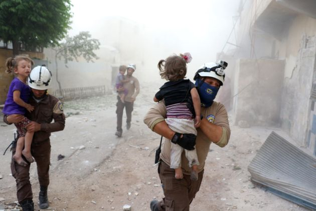 Search and rescue team members carry wounded children after an Assad forces' airstrike hit residential...