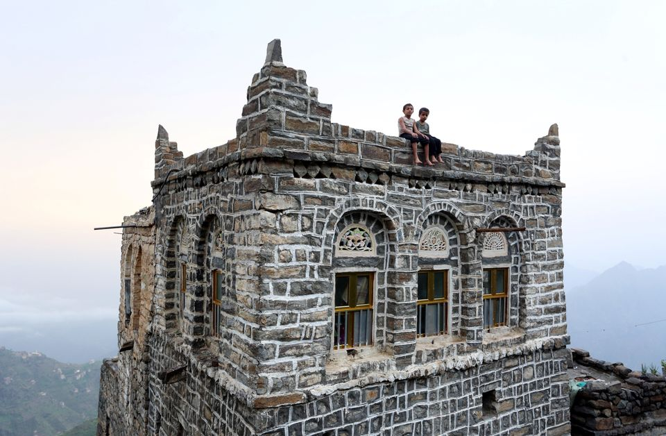 Young boys sit on the roof of their home in the mountains of Yemen's Jafariya district...
