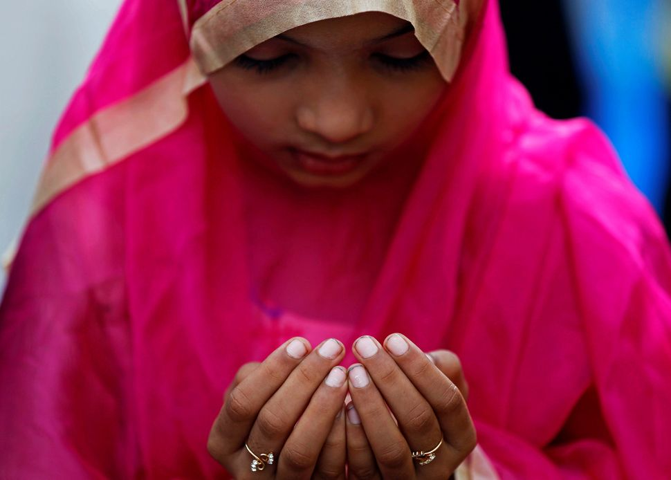 A girl offers Eid al-Adha prayers on a street outside a railway station in Mumbai, India.