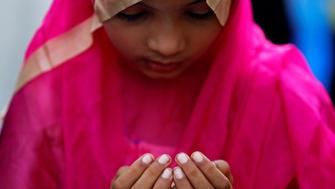 A girl offers Eid al-Adha prayers on a street outside a railway station in Mumbai, India September 13, 2016. REUTERS/Shailesh Andrade