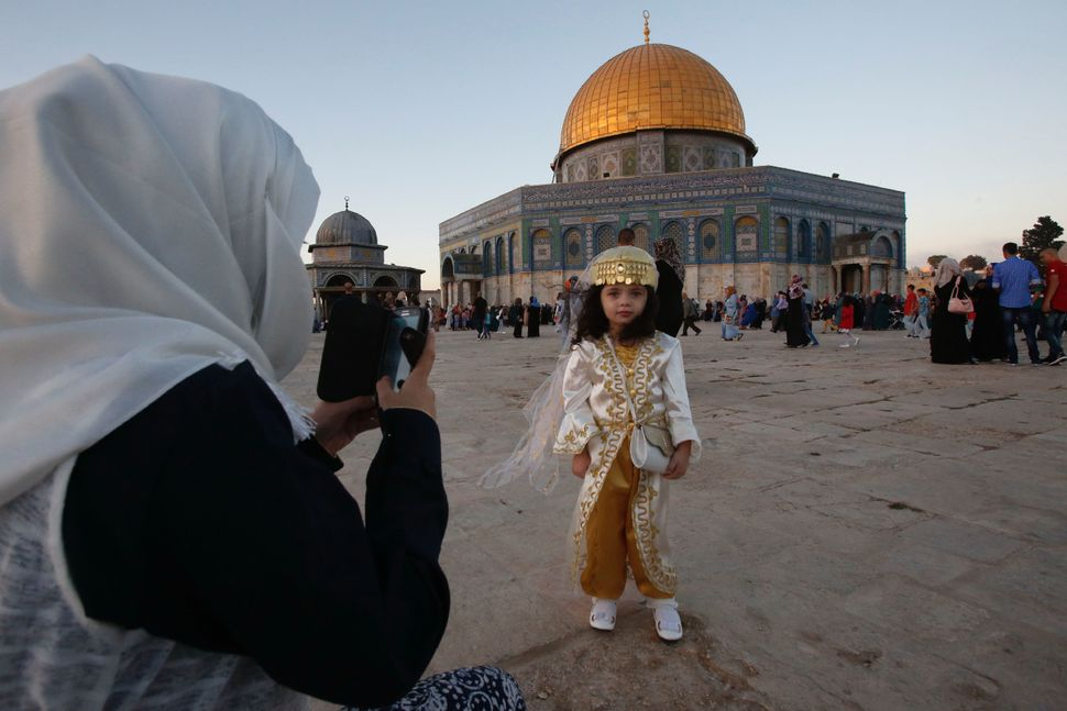 A Palestinian woman takes a picture of her daughter on the occasion of Eid al-Adha, in Jerusalem, Palestine, Sept. 12, 2