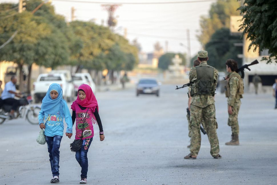 Syrian girls walk near the Ebul Hasan mosque in Jarablus, where Eid al-Adha prayers were held under supervision of members of