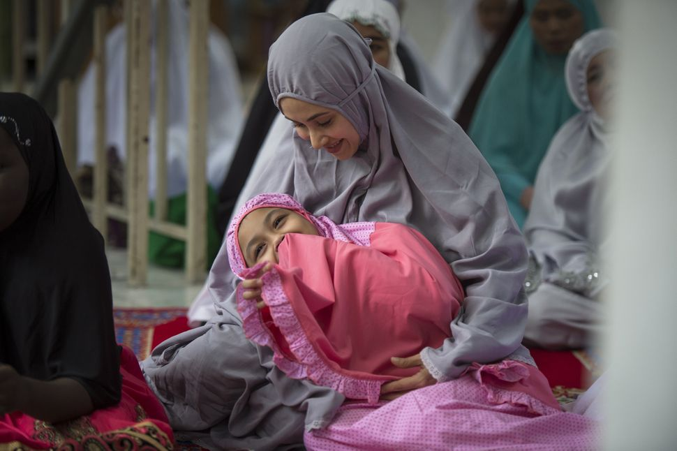 A mother and daughter wait for Eid prayers to begin at the Haroon mosque in Bangkok, Thailand, Sept. 12, 2016.
