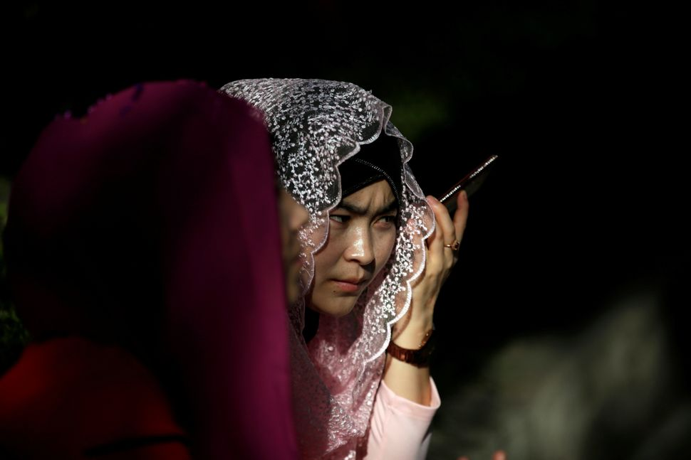 A Muslim woman uses her phone before Eid prayers outside a mosque in Shanghai, China, Sept. 12, 2016.