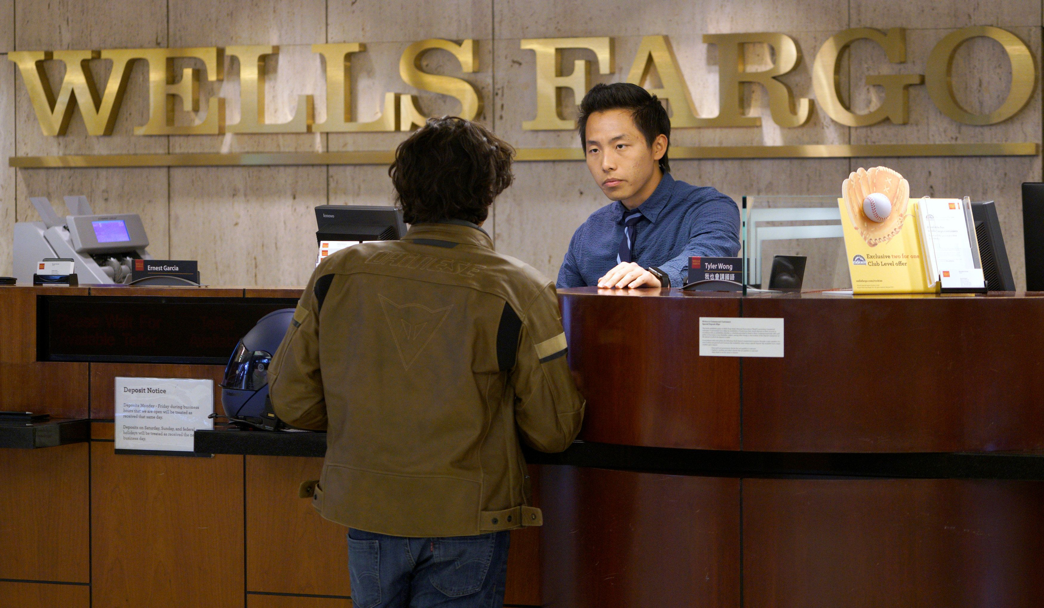 Bank Teller Tyler Wong talks to a customer at the Wells Fargo bank in Denver, Colorado, U.S. April 13, 2016.