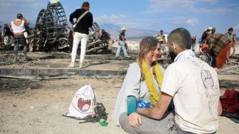 Two participants sit near the burned remains of the Man as approximately 70,000 people from all over the world gathered for the 30th annual Burning Man arts and music festival in the Black Rock Desert of Nevada, U.S. September 4, 2016. REUTERS/Jim Urquhart FOR USE WITH BURNING MAN RELATED REPORTING ONLY. FOR EDITORIAL USE ONLY. NOT FOR SALE FOR MARKETING OR ADVERTISING CAMPAIGNS. NO THIRD PARTY SALES. NOT FOR USE BY REUTERS THIRD PARTY DISTRIBUTORS
