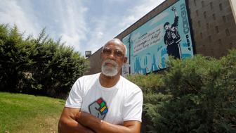 John Carlos, participant of the 1968 Olympics, stands in front of a mural made by students on the campus, at Palm Springs High School, where he is a teacher and counsellor in Palm Springs, California July 11, 2012. Picture taken July 11, 2012. REUTERS/Alex Gallardo (UNITED STATES - Tags: SPORT OLYMPICS)