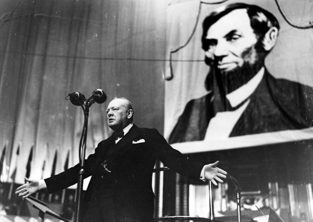 Speaking at the Albert Hall in front of a large picture of Abraham Lincoln in