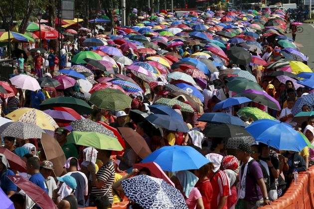 Devotees wait in line with umbrellas in the scorching heat for their turn to hold and kiss the foot of...