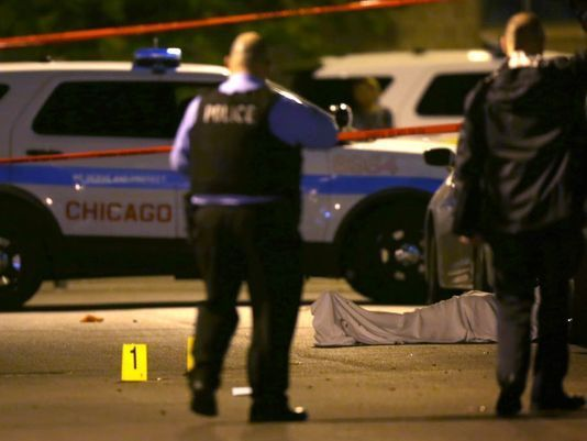 In this May 30, 2016, photo, police work the scene where a man was fatally shot in the chest in Chicago's Washington Park nei