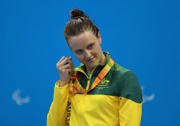 Ellie Cole of Australia holds her silver medal up to her ear on the podium at the medal ceremony for...
