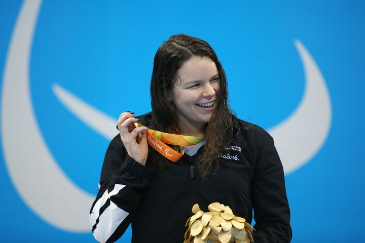 Gold medalist Mary Fisher of New Zealand shakes her medal on the podium for the Women's 100m Backstroke.