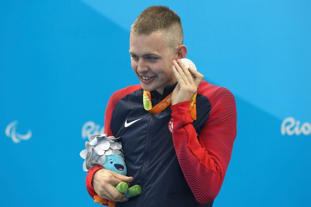 Silver medalist Tharon Drake of the United States listens to the sound of his medal on the podium at...