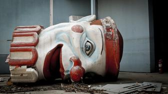 Stylized image of a fallen clown head in an abandoned new orleans theme park.  Smashed and scatters amongst Katrina rubble.  this image was taken in late 2011 and is under no copyright