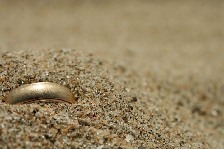 A gold ring lost in the sand.