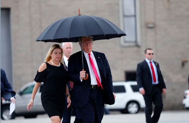 Republican presidential nominee Donald Trump walks in the rain with Florida Attorney General Pam Bondi, as he arrives at a ca