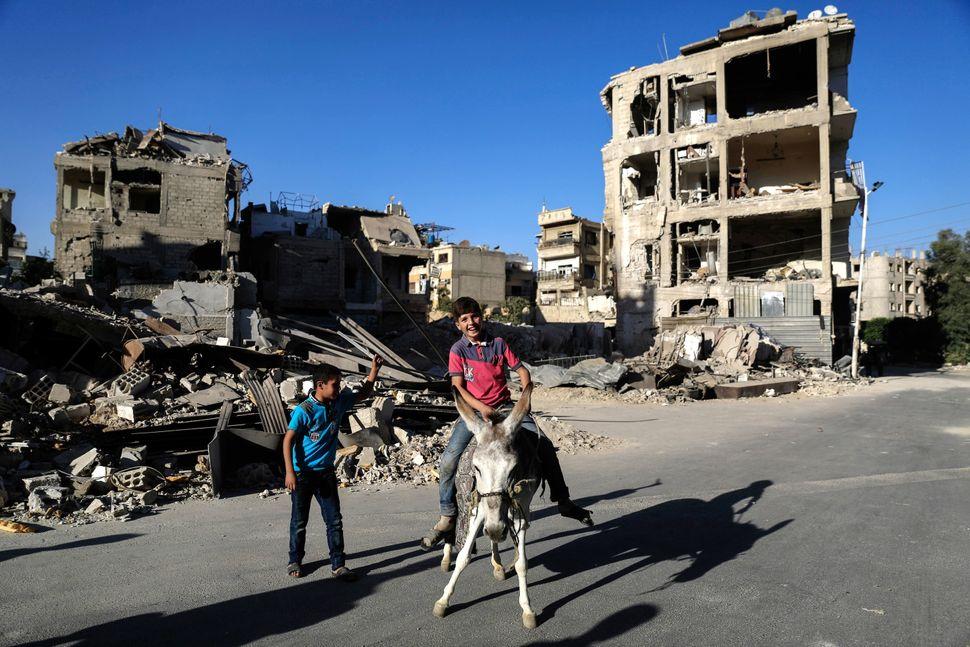 A Syrian boy rides a donkey in Douma.