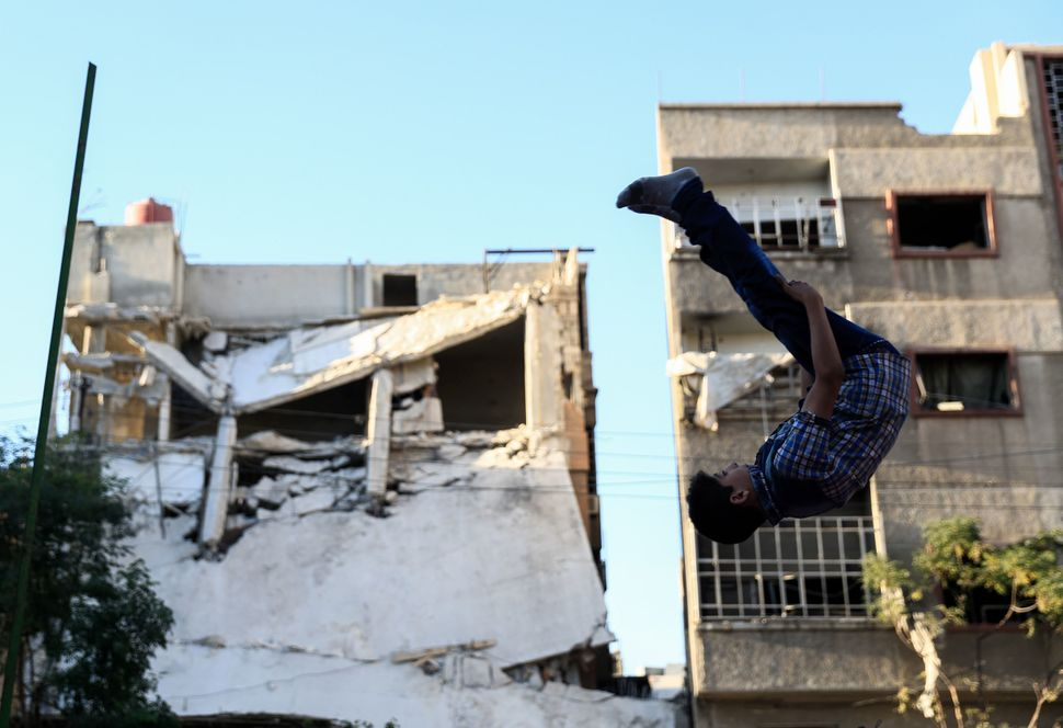 A Syrian boy jumps as he plays in the rebel-held town of Douma, on the eastern edges of the capital Damascus, on the second d