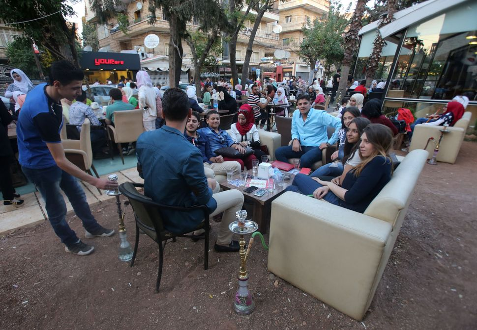 Syrian youths sit at a cafe in the government-held Mogambo neighborhood of Aleppo.