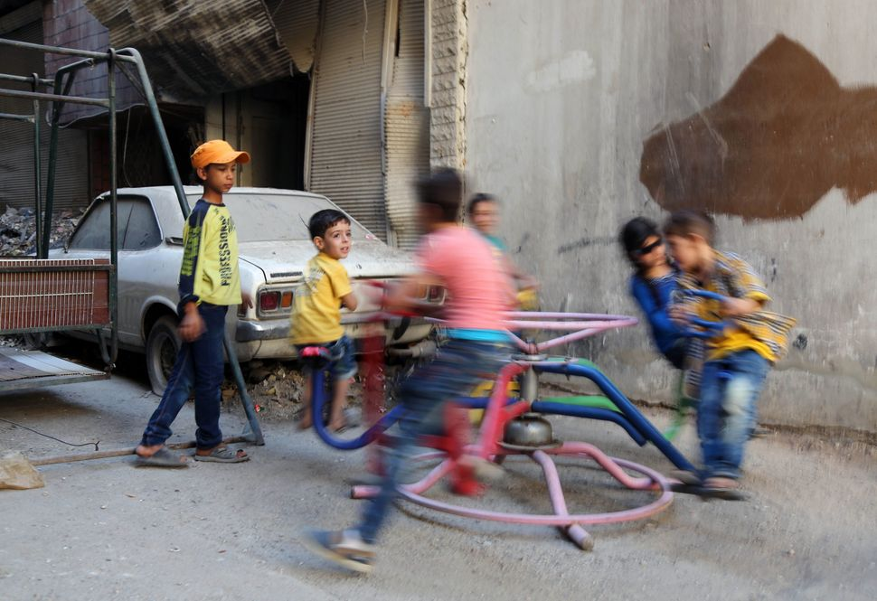 Syrian children play on a ride in the Syrian rebel-held town of Arbin, in the eastern Ghouta region on the outskirts of the c