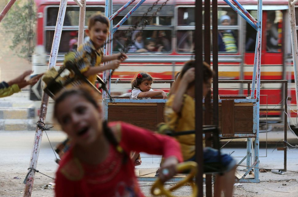 Smiling Syrian children play on swings in Arbin.