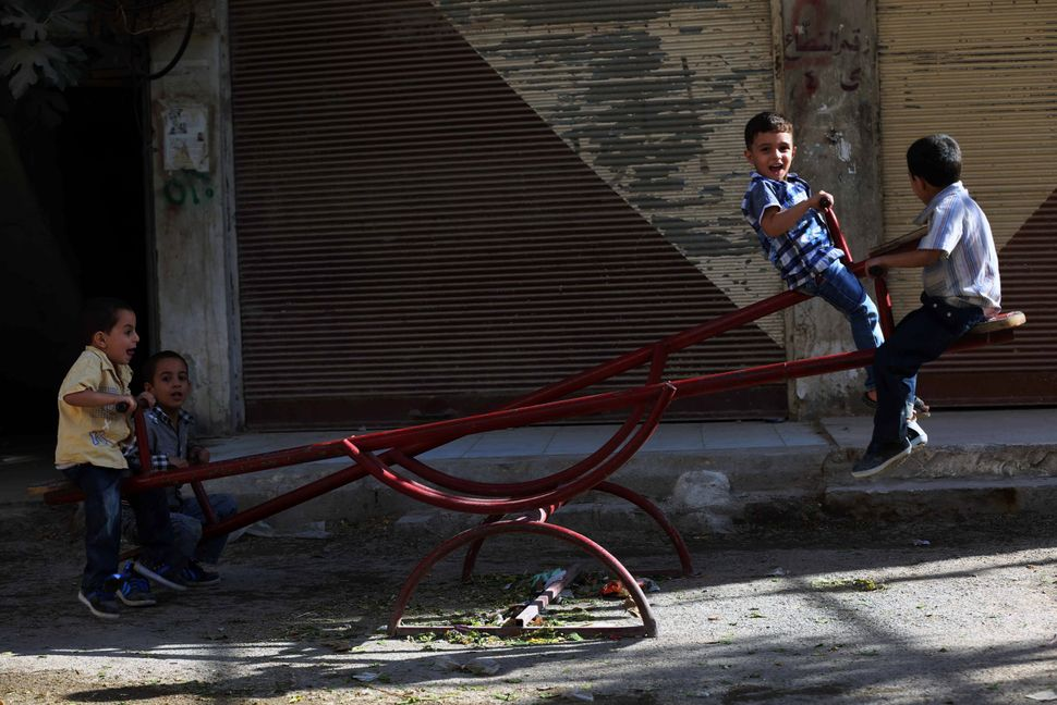 Syrian boys play on a see-saw in Arbin.