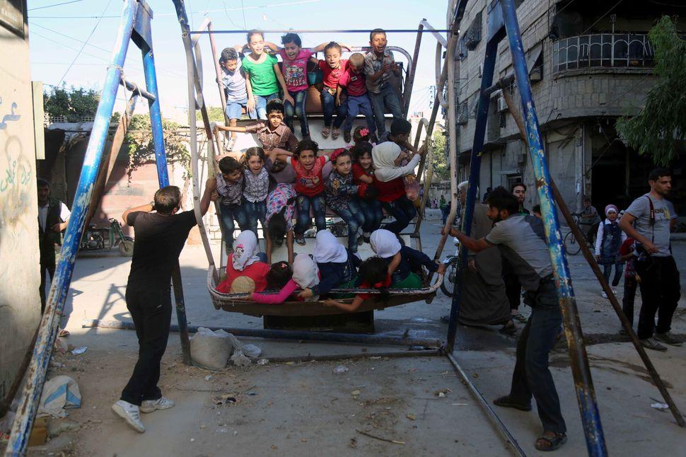 Syrian children ride an attraction in Arbin.