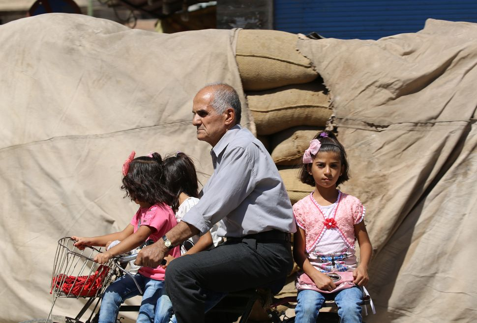 A Syrian man carries three girls on a bicycle in the northeastern city of Qamishli.