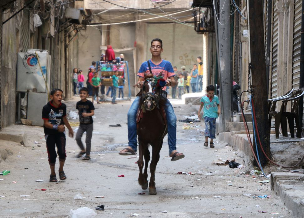 A boy rides a horse as children play in the street in a rebel-held area of the northern Syrian city of Aleppo as they celebra