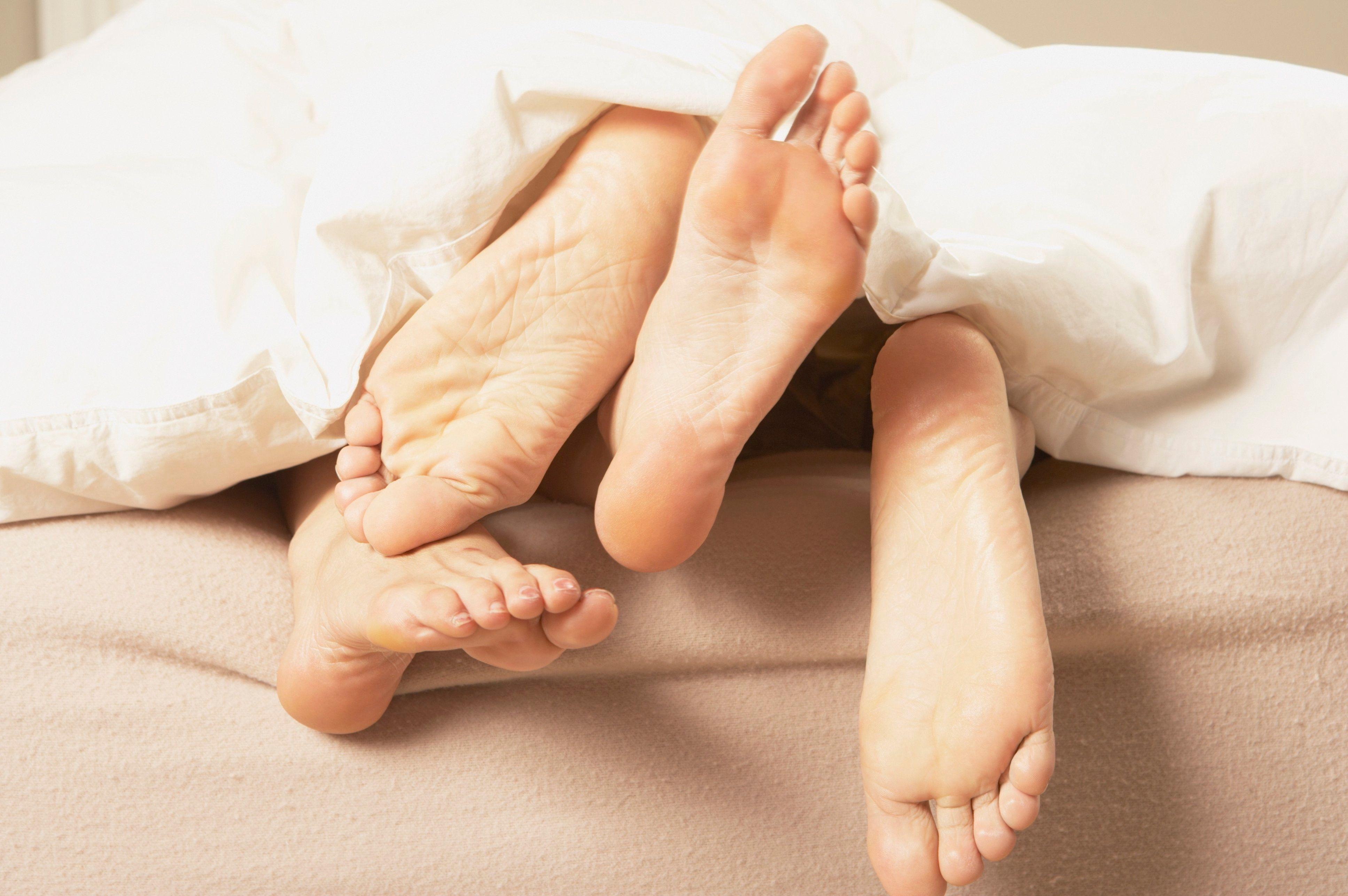Close up of couple's bare feet sticking out from under the covers