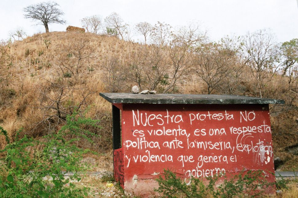 "Bus stop at the Ayotzinapa Normal School. Grafitti on the structure reads, ""Our protest is not violent, it is a political res"