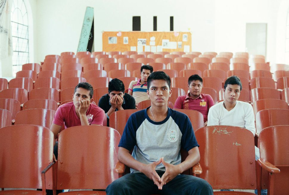 Student survivors of the Iguala attacks and disappearances sit in the auditorium of the Ayotzinapa Normal School on March 16,