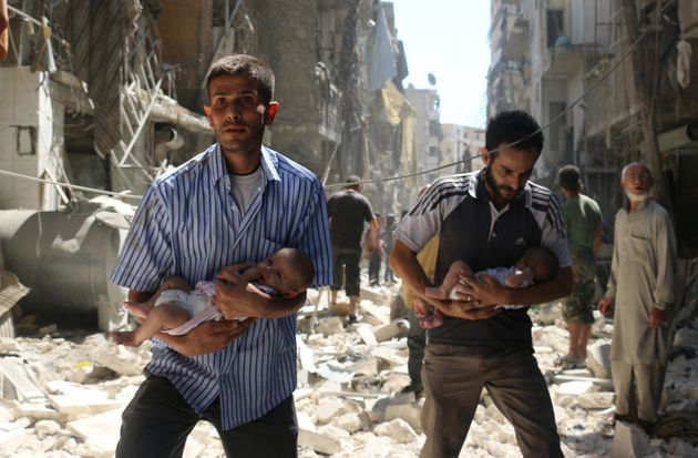 Syrian men carry babies through the rubble of destroyed buildings following a reported air strike...