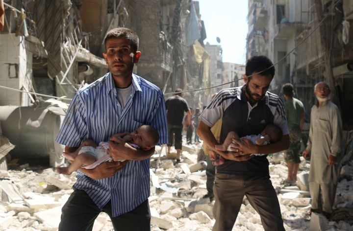 Syrian men carry babies through the rubble of destroyed buildings following a reported air strike on rebel-held Aleppo o
