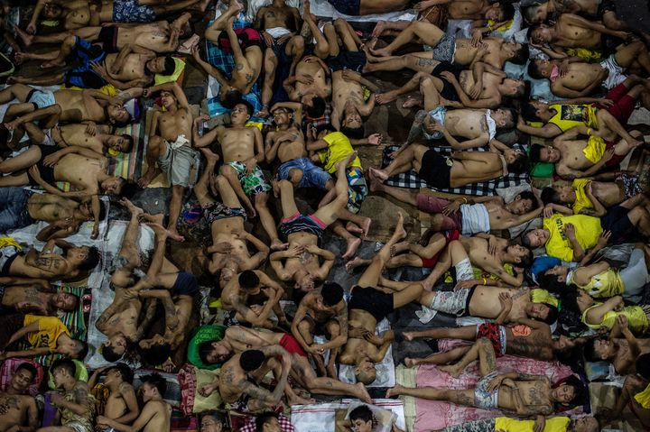 Inmates sleep on a basketball court inside the Quezon City jail in Manila on July 19. Thousands are packed into a f