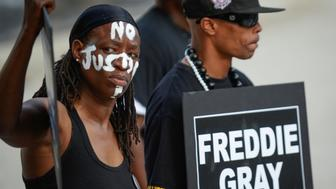 Angel Selah (L) and local artist PFK Boom gather to remember Freddie Gray and all victims of police violence during a rally outside city hall in Baltimore, Maryland, U.S., July 27, 2016.  REUTERS/Bryan Woolston